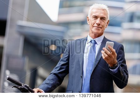 Successful businessman on bicycle with mobile phone