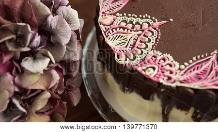 Sponge cake with mehendi patterns on glass stand. Close-up.