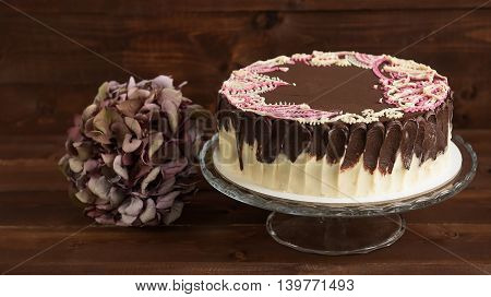 Cake with mehendi patterns on the glass stand. Wooden background.