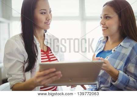 Close-up of female colleagues discussing with digital tablet in creative office