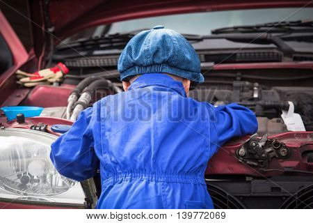 Little boy in blue workwear overall in front of open engine compartment doing some maintenance work at the car