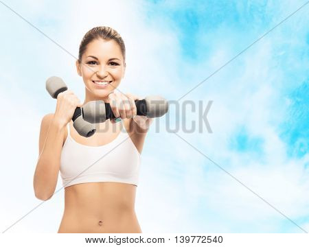 Sporty, athletic and attractive woman with a dumbbells over heaven background. Sport, dieting and healthy lifestyle concept.