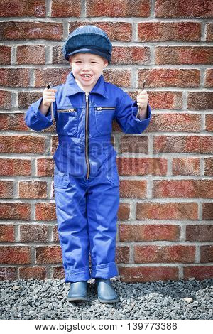 Small boy dressed with blue workwear overall stand in front of red brick wall hold two tools in his hands and smiles (copy space)