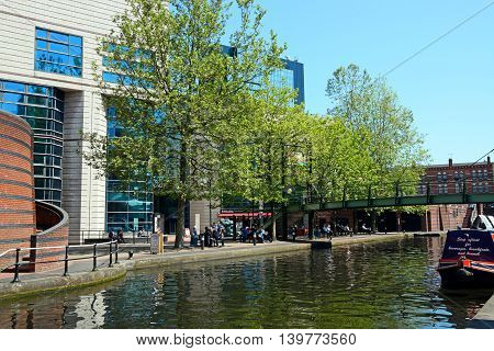 BIRMINGHAM, UNITED KINGDOM - JUNE 6, 2016 - View towards the rear of the ICC with people relaxing in the foreground at Brindleyplace Birmingham England UK Western Europe, June 6, 2016.