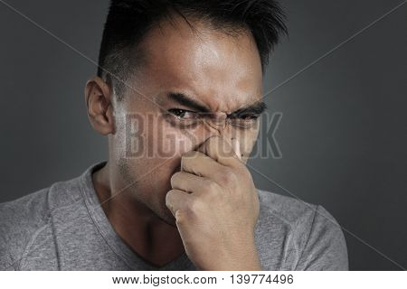 portrait of a man pinching his nose on a gray background