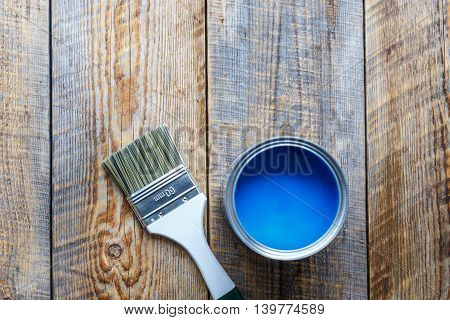 open jar with blue paint and brush on the wooden background top view close up