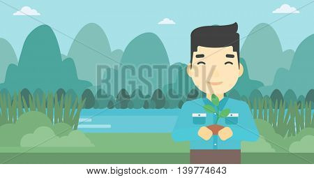 An asian young man holding in hands a small plant in soil on the background of landscape with mountains and river. Vector flat design illustration. Horizontal layout.