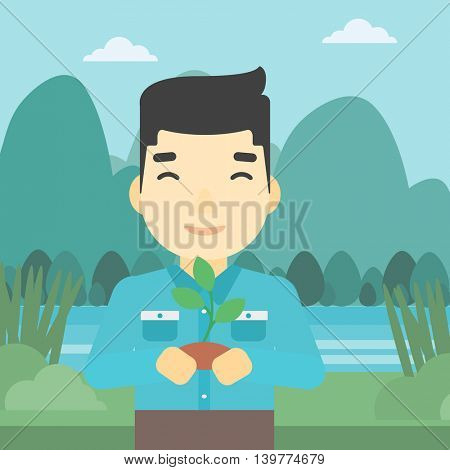 An asian young man holding in hands a small plant in soil on the background of landscape with mountains and river. Vector flat design illustration. Square layout.