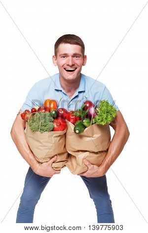 Smiling young man holding shopping bags full of groceries isolated at white background. Healthy food shopping. Paper package with vegetables and fruits, happy male buyer came from market