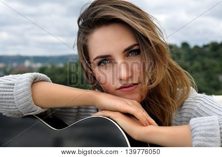 Portrait of a beautiful girl who leaned on the guitar