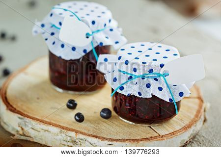 Fresh blueberry homemade jam in jar with tag and berry on  wood background. healthy organic and vegan food