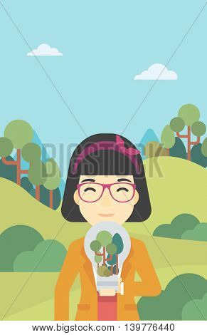 An asian woman standing on the background of green forest and holding in hands a big lightbulb with trees inside. Green energy concept. Vector flat design illustration. Vertical layout.