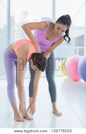 Full length of trainer working with woman at fitness studio