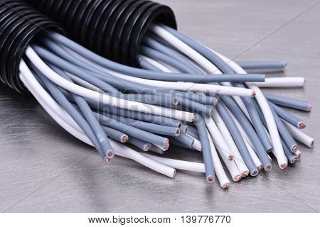 Electric cables in corrugated plastic pipes on metal surface