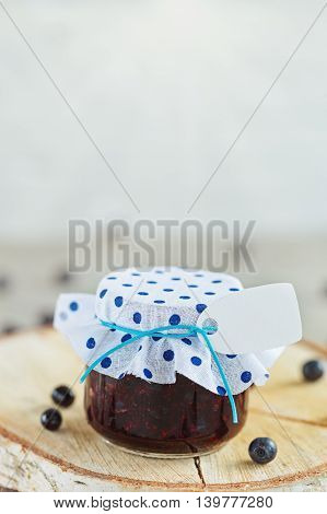 Fresh blueberry homemade jam in jar with tag and berry on  wood background. healthy organic and vegan food.