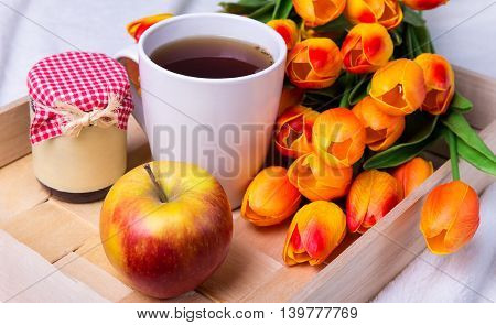 Close Up Of Tray With Cup Of Tea, Jar Of Jam Or Honey, Apple And Flowers