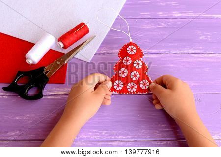 Child holds a red felt Christmas tree ornament his hands. Red felt fur tree decorated with white balls. Christmas crafts idea for kids. Felt sheets, scissors, thread on wooden background