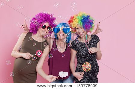 Group of young women disguised for a party with candies ballons and wigs.