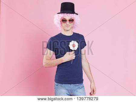 Funny portrait of a young man wearing a carnival accessory over a pink background.