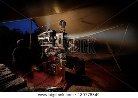 vintage old film projector with reels in dark tent at outdoor theatre