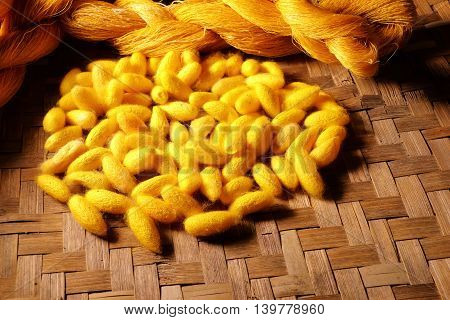 silk cocoons and raw silk threads in basket