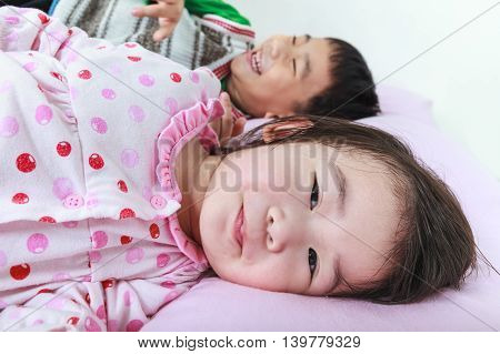 Closeup asian siblings having happy in bed before sleeping. Conceptual image about loving and bonding of sibling. Happy family spending time together.