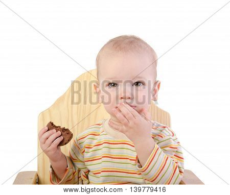 Cute boy sitting on a chair and eating cookie