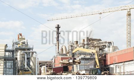 industrial plant of a furniture factory with smoking smokestackstubessiloscrane and trunks.