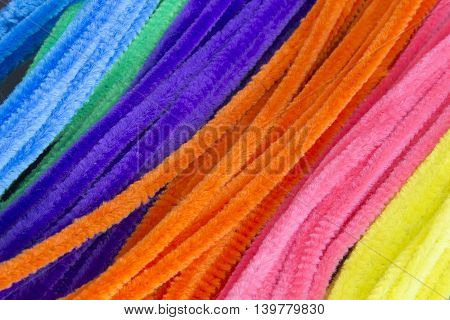 This is a photograph of Blue,Green,Purple,Orange,Pink and Yellow pipe cleaners background
