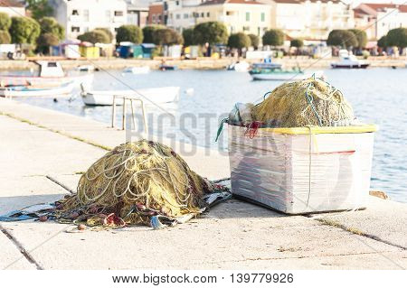 A large fishing net piled on the dock