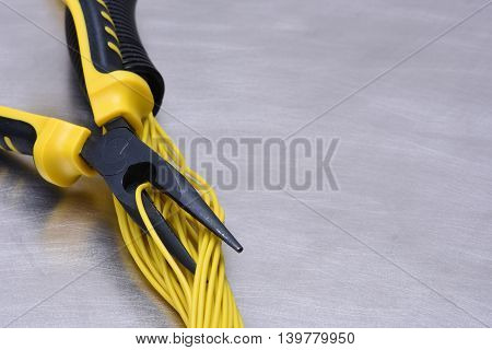 Electrical tools and cables on metal surface with place for text
