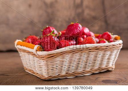 Ripe red strawberries. Wicker basket filled with berries. Ingredient of dietary breakfast. Taste of summer season.