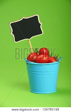 Blue Bucket Of Cherry Tomatoes With Sign On Green