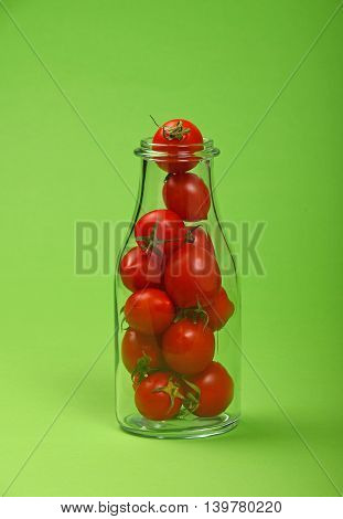 Red Cherry Tomatoes In Glass Bottle Over Green