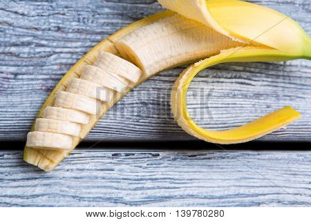 Banana on gray wooden surface. Top view of banana slices. Fresh tropical fruit. Sweet gift of nature.