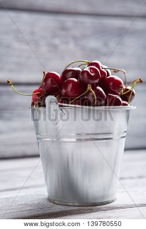 Bucket filled with cherries. Bucket on light gray surface. Fruit that eases digestion. Grown without pesticides.