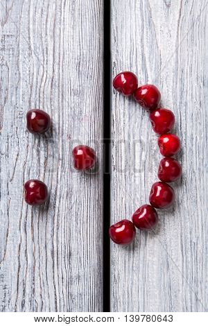 Smiley face made of cherries. Red fruit on wooden background. Stay healthy and be happy. Art is closer than ever.