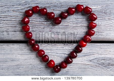 Heart made of cherries. Fruit on gray wooden background. Keep your heart healthy. Wealth of the garden.