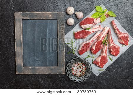 Raw lamb chops with salt, pepper, rosemary  on paper over black background. chalk board near. Top view,  copy space.