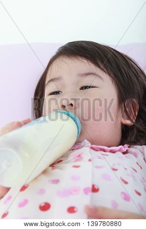 Closeup Cute Asian Girl Suck Up Milk Bottle. Drinking Milk For Good Health.