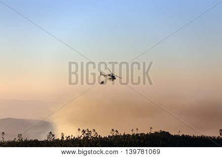 Fire-fighting Helicopter With A Water Bucket Fighting A Fire On A Hillside