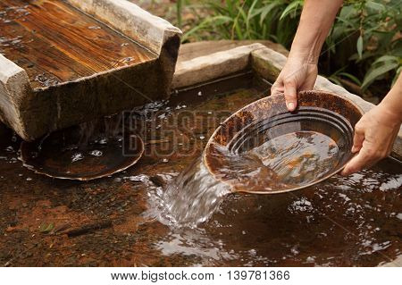 Panning for gold with pan and sluice