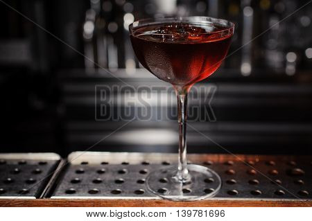 dark cocktail on a dark bar setting. no people