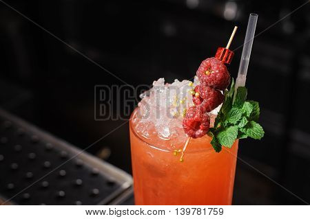 Refreshing red cocktail beverage with a sprig of fresh mint leaves and raspberries at the bar