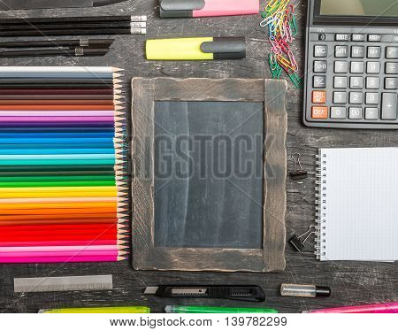 School supplies on blackboard background, top view, copy space