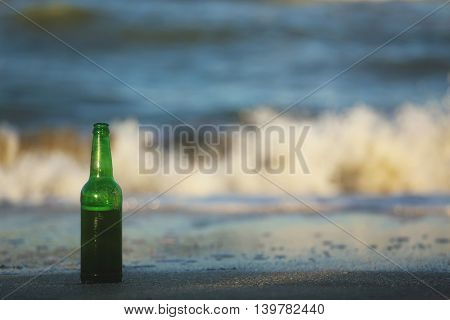Green beer bottle sitting in the sand on the seashore.
