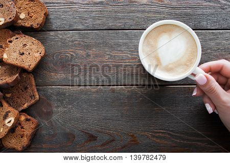 Cup of cappuccino and sweet rye bread slices on wooden table, copyspace. Breakfast in cafe, weekend in Paris