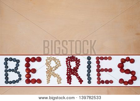 wooden background with text formed with berries - strawberry raspberry red and white currant blueberry