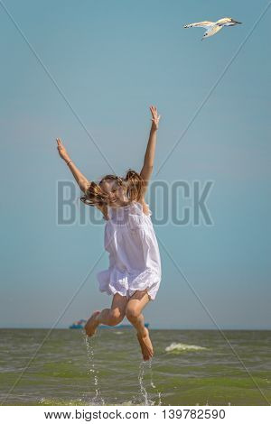 Happy girl in a white sundress jumping over the water on the beach against the sea and blue sky with flying seagull on a hot summer day
