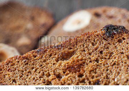 Rye bread background, slices with nuts and raisins close-up. Cereal bakery backdrop